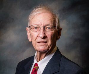 Commissioner Bobby Dunlap is solemn in front of a shaded dark background wearing a black suit coat, white button down collared shirt, and a red and gold necktie.