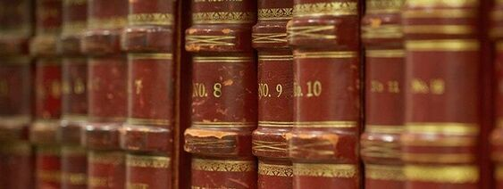 A closeup picture of the middle third of the spines of about eleven volumes of old archived books, titled No. 8, No. 9, No. 10, with other volumes' titles' blurred.  The books are a dark red with shiny gold writing as well as gold detail and filigree embossing.