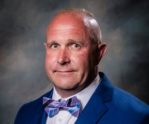 Commissioner Gary Eddings smiles in front of a shaded dark background wearing a bright indigo suit coat, a white collared button down shirt, and a purple and blue striped bowtie.