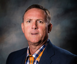 Commissioner Jack Vincent appears solemn in front of a shaded dark background wearing a dark navy suit jacket and a orange, navy, and white plaid button down collared shirt.