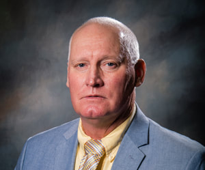 Commissioner Larry Hudson wears a slight smile in front of a shaded dark background wearing a gray suit coat, a pastel yellow collared button down shirt, and a white and shades of gold shiny and striped print necktie.