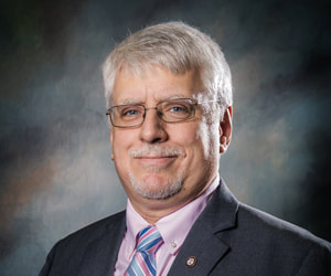 Commissioner Scott Fortner smiles in front of a shaded dark background wearing a dark charcoal suit coat with lapel pin, a light pink collared button down shirt, and a light blue and pink striped print necktie.