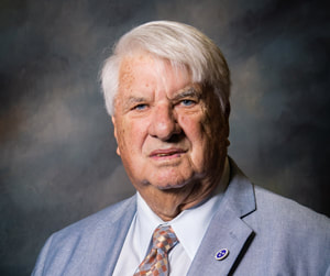 Commissioner Dale Overton appears solemn in front of a shaded dark background wearing a light gray suit coat with lapel pin, white collared button down shirt, and a multicolored spotted necktie.