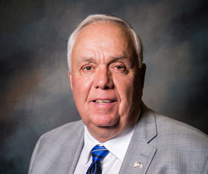 Commissioner David Hawks smiles in front of a shaded dark background wearing a light gray plaid suit coat with lapel pin, white collared button down shirt, and a bright blue necktie with a yellow stripe on the knot.