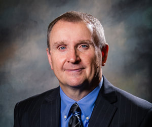 Commissioner Greg Usery smiles in front of a shaded dark background wearing a black suit coat, a blue collared button down shirt, and a back and blue striped print shiny necktie.