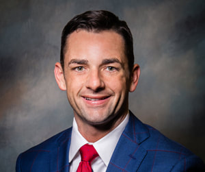 Mayor Bynum smiles before a dark shaded multicolored background wearing a blue suit, white collared button down shirt, and a bright red tie.